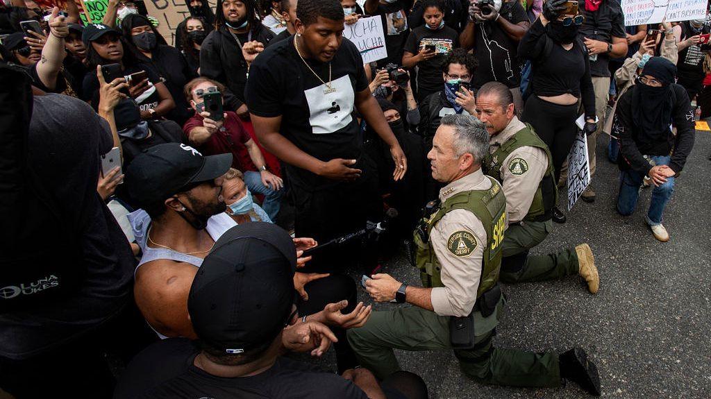 Riverside, Kalifornia. Policjanci przyklękają na jedno kolano w geście solidarności z protestującymi