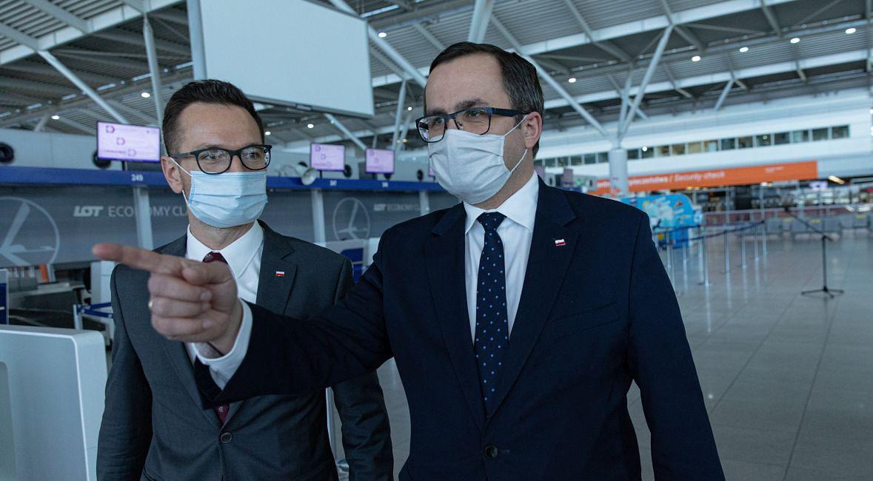 Wiceministrowie infrastruktury Waldemar Buda (z lewej) i Marcin Horala podczas konferencji prasowej w sprawie pomocy lotniskom poszkodowanym w związku z epidemią koronawirusa. Lotnisko Okęcie, 22 maja 2020 roku